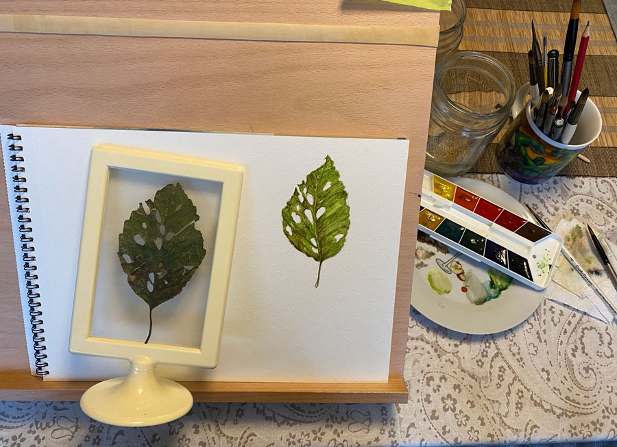 Art desk with leaf painting on sketchpad, watercolour paints and brushes